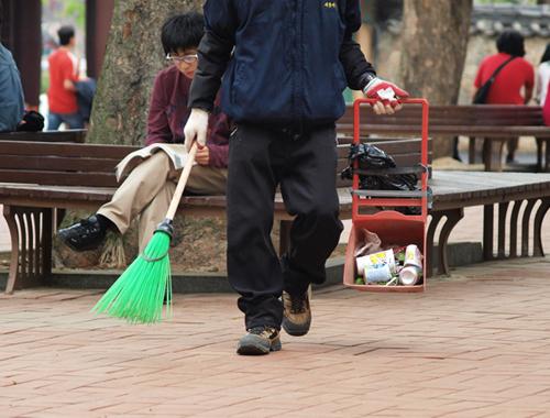 대학 교정에서 빗자루를 들고 청소하러 다니는 노동자의 모습