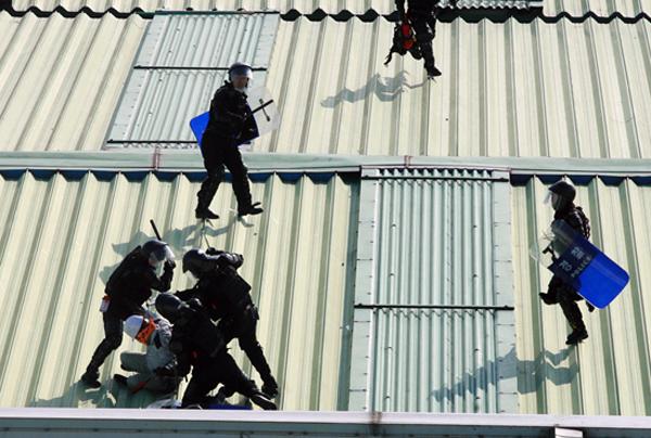쌍용차 파업 당시 노동자를 폭행하고 있는 경찰의 모습(사진=참세상)