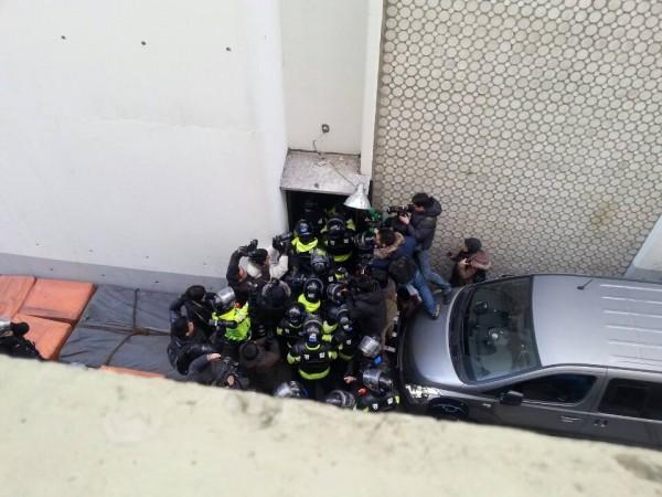 쪽문으로 강제진입하고 있는 경찰들