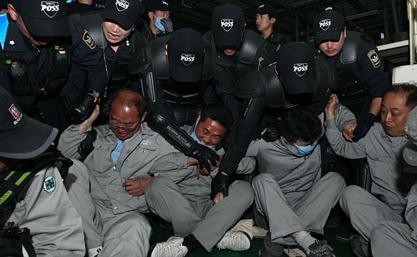 노동자를 강제로 끌어내고 있는 경찰들 모습(금속노조)